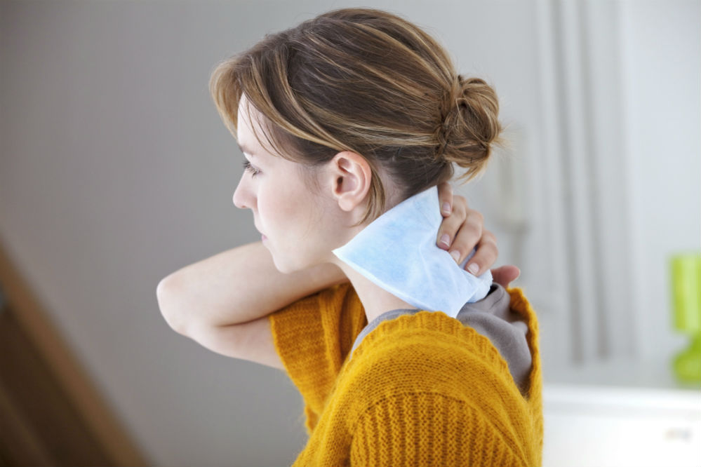 woman using heating pad on her neck