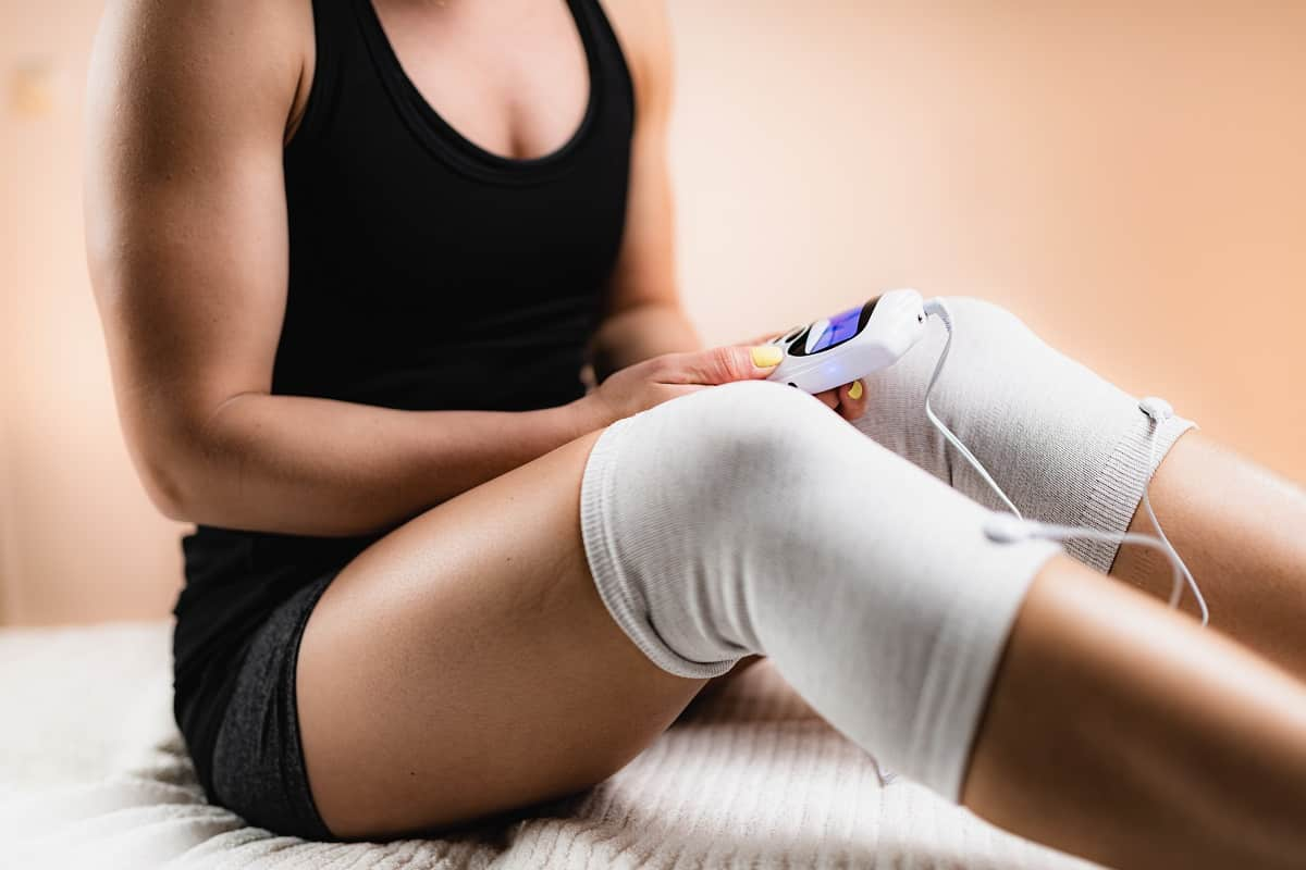 woman using a knee heating pad