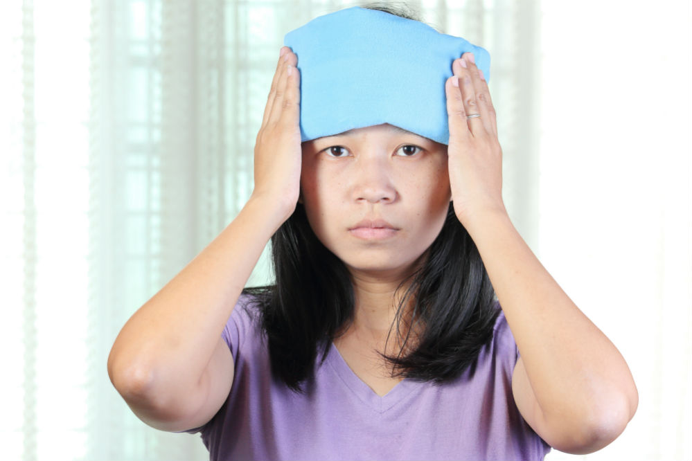 Woman with heating pad on her head