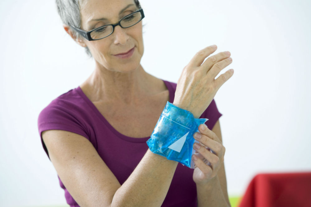 Woman using heating pads on wrist