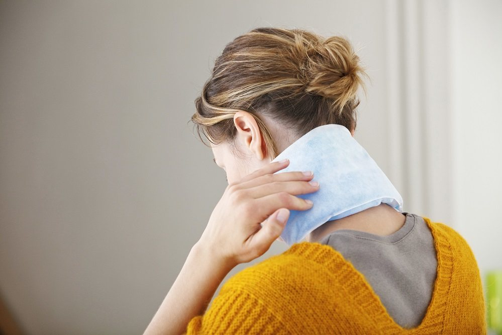 Woman using heating pads on neck