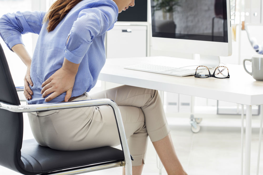 woman sitting on chair with both hands on lower back